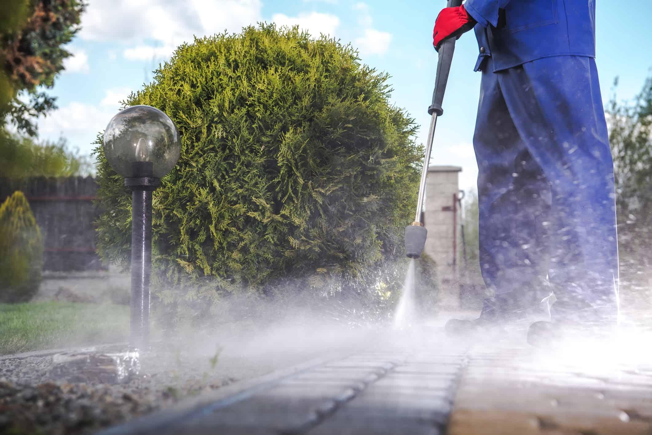 Zahradník čistí zámkovou dlažbu tlakovým čističem